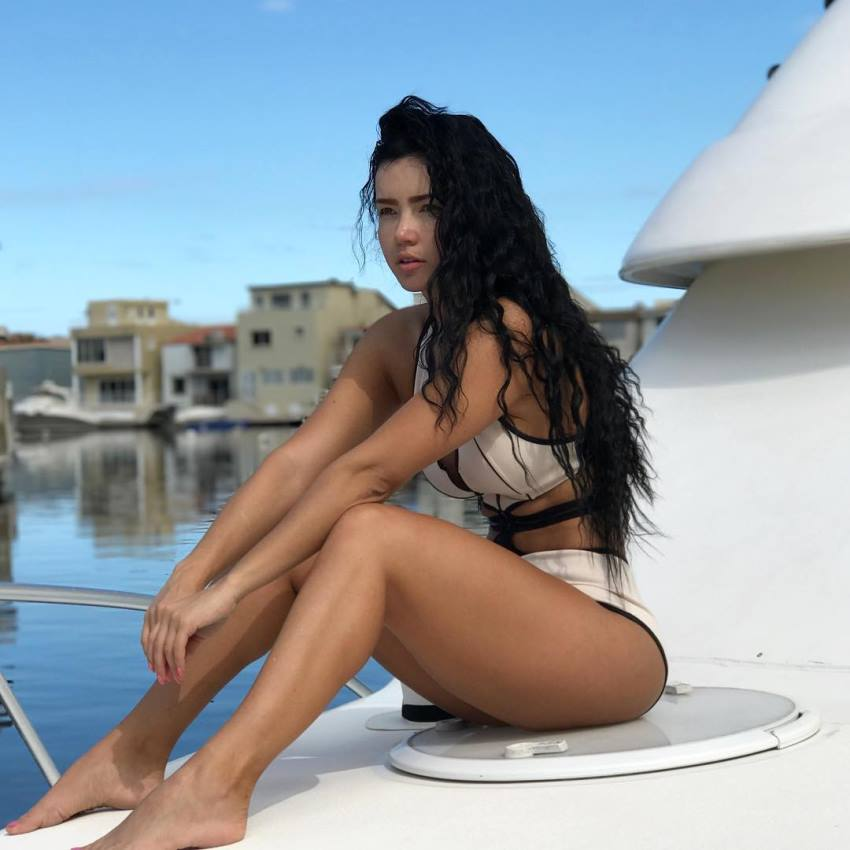 Ariana James sitting on a boat looking fit and lean
