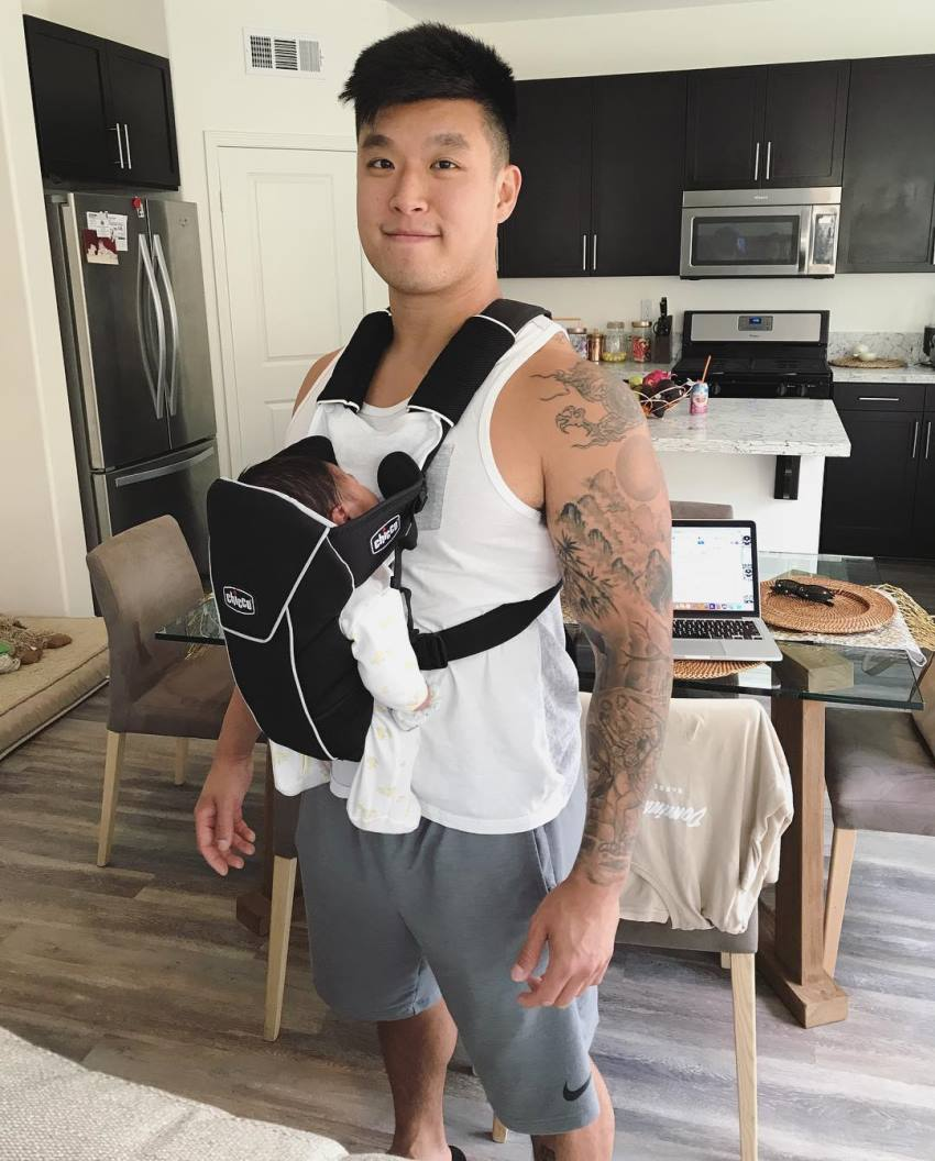 Bart Kwan carrying his child in a front facing baby carrier and smiling at the camera