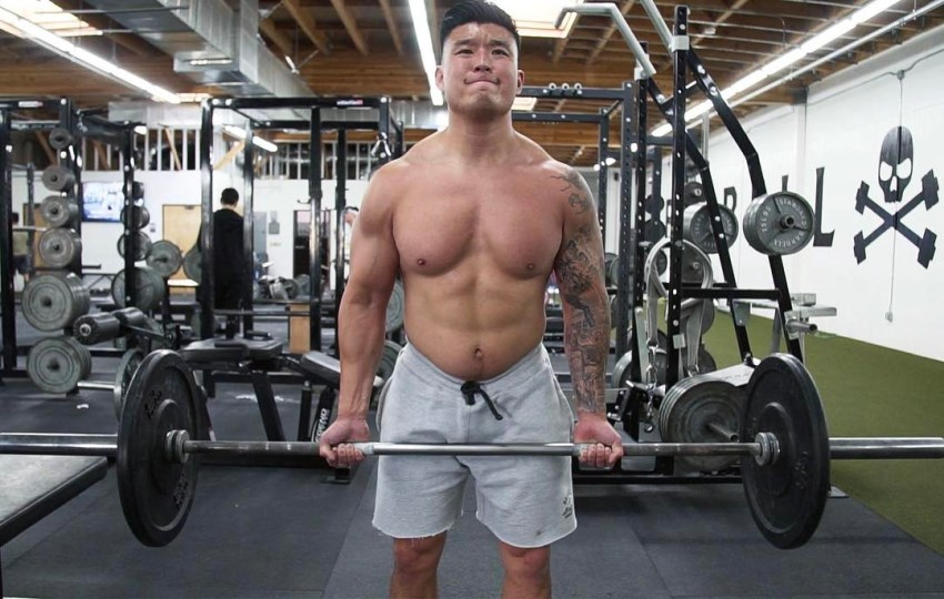 Bart Kwan doing heavy barbell curls in the gym