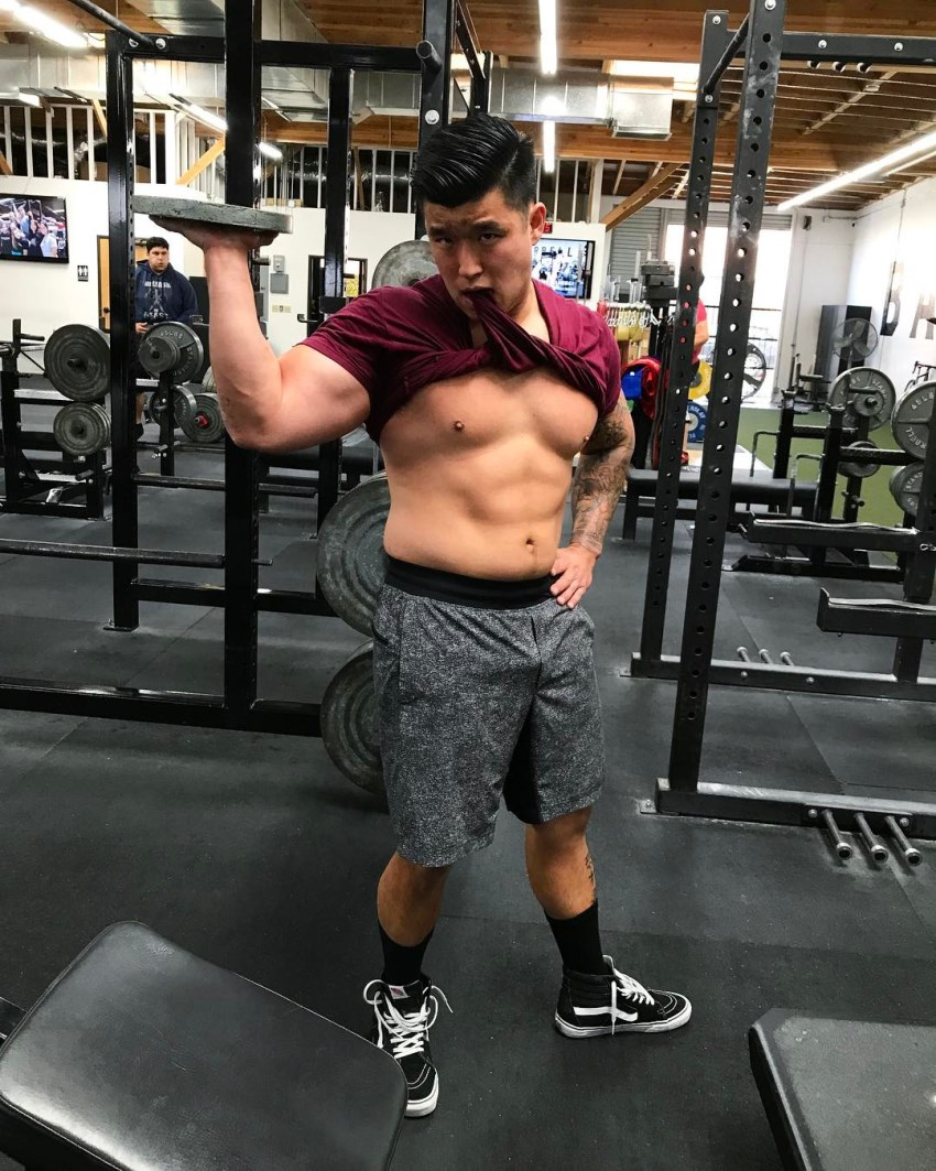 Bart Kwan holding a weight plate in the gym and showing his abs in a humorous way