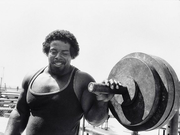 Bill Pettis in his prime, holding onto a barbell for the 1984 Olympics poster.