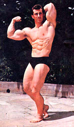 Bob Gajda flexing his biceps and abs outdoors