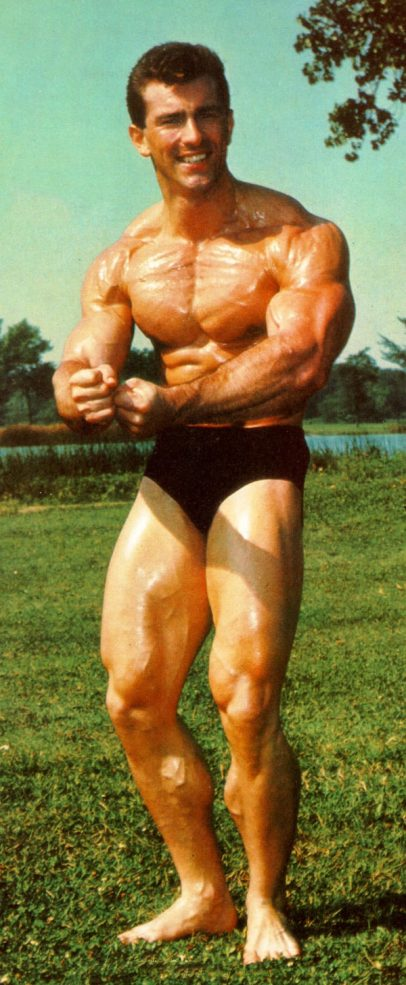 Bob Gajda in a most muscular pose outdoors, standing on the grass, and posing for a photo