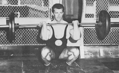Bob Gajda in a squat position with a weighted barbell over his shoulders, preparing to do a movement