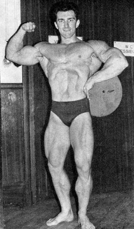 Bob Gajda doing a vacuum pose and one-arm biceps flex on the stage