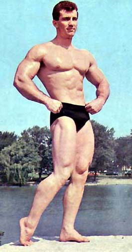 Bob Gajda posing outside by the lake, looking muscular