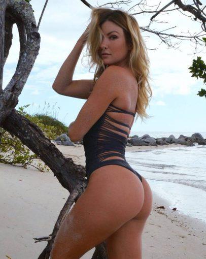 Cassandre Davis by the tree near a beach, looking fit