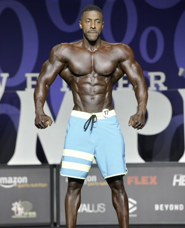 Coty Hart posing on the stage spreading his lats wide