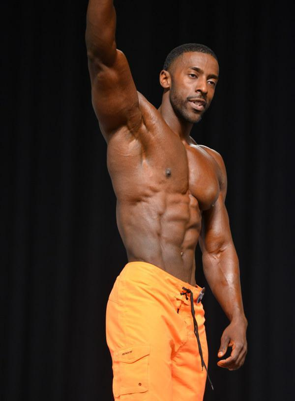 Coty Hart waving at the audience showing his ripped abs on the stage