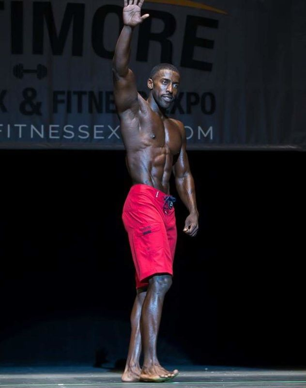 Coty Hart standing on the stage in red shorts waving at the audience