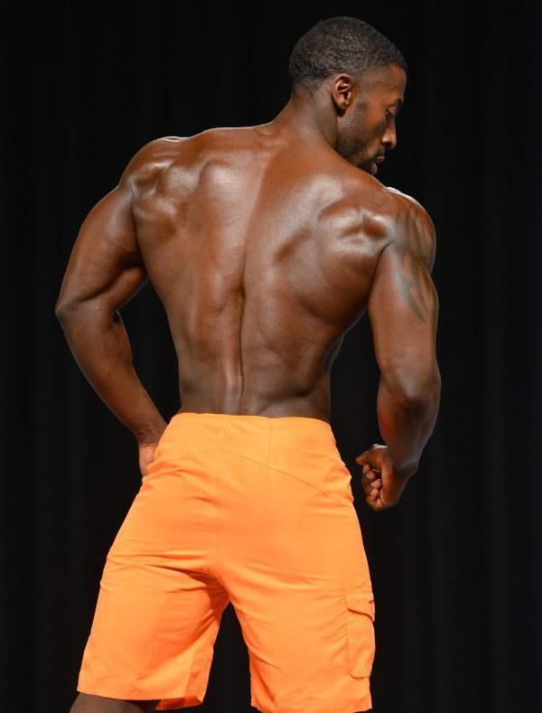 Coty Hart showing his ripped back on the Men's Physique stage