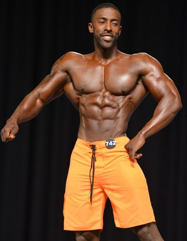 Coty Hart posing on the Men's Physique stage with a smile on his face
