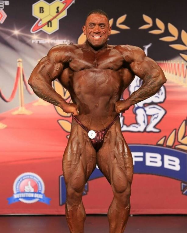 Darryn Onekawa doing a front lat spread on the bodybuilding stage in front of the audience