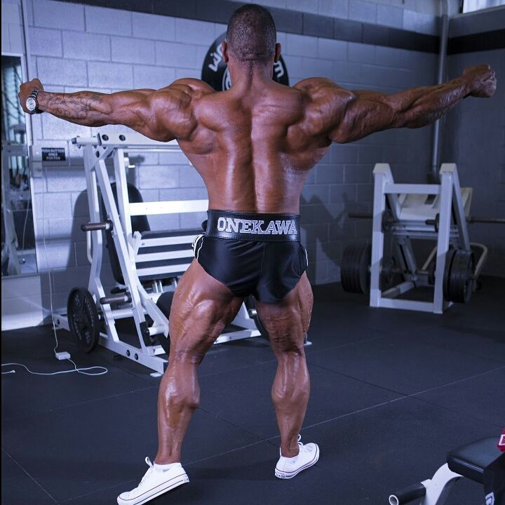 Darryn Onekawa flexing his back and arms for the camera