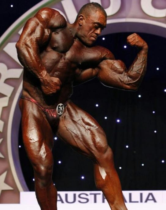 Darryn Onekawa flexing his biceps on the bodybuilding stage