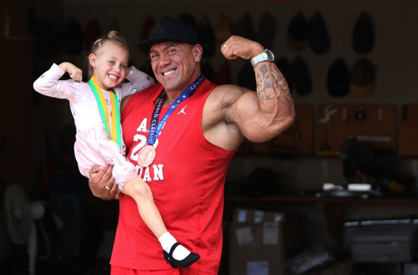 Darryn Onekawa flexing his biceps while holding his daughter