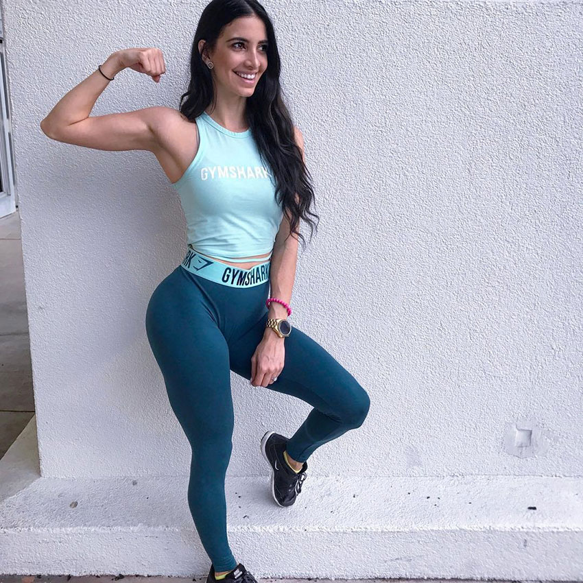 Diana Ruiz flexing her arm, leaning against a wall.