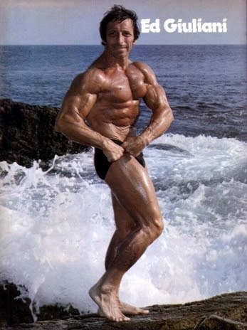 Eddie Giuliani flexing by the sea, looking ripped