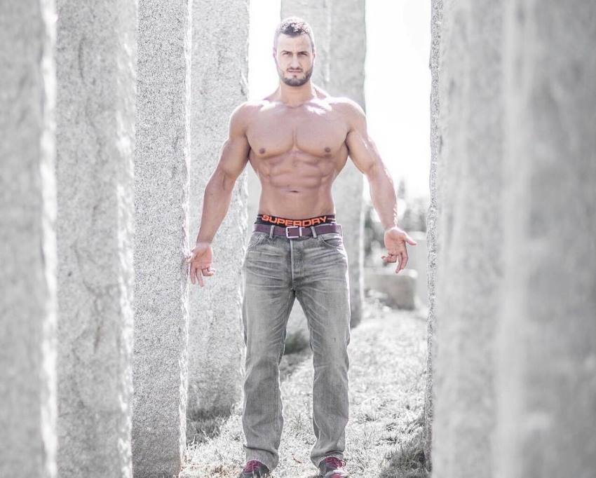Emil Goliath posing shirtless in grey jeans for the camera