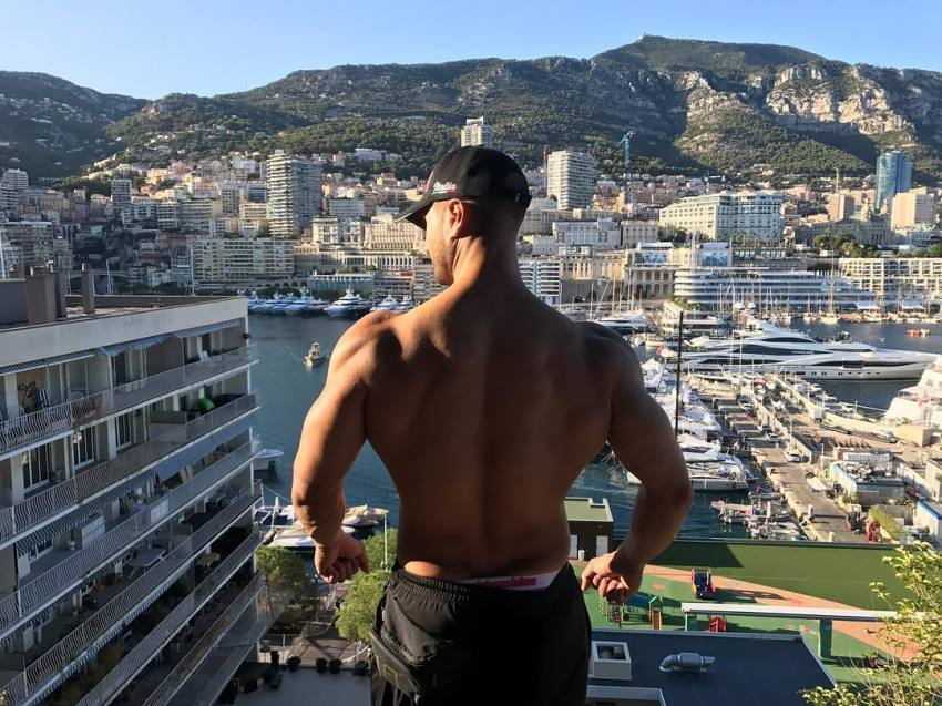 Emil Goliath overlooking a city from skyscraper rooftop, showcasting his lean back