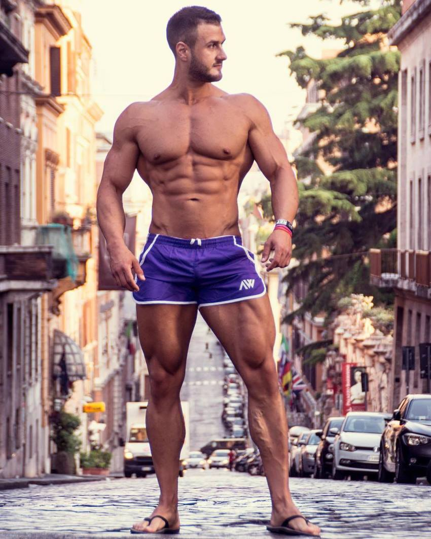 Emil Goliath posing shirtless in the middle of a street in his pink shorts