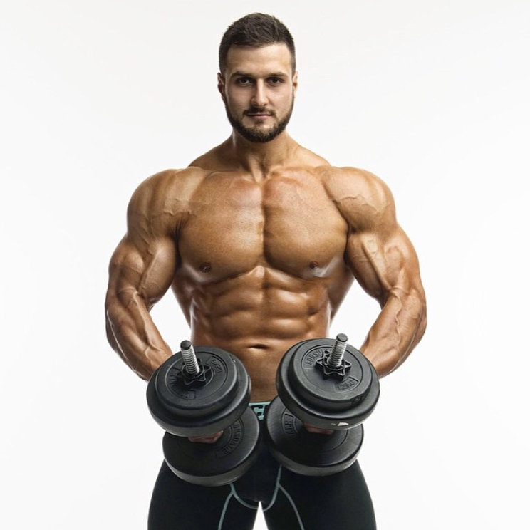 Emil Goliath posing shirtless with two dumbbells in his hands, looking muscular