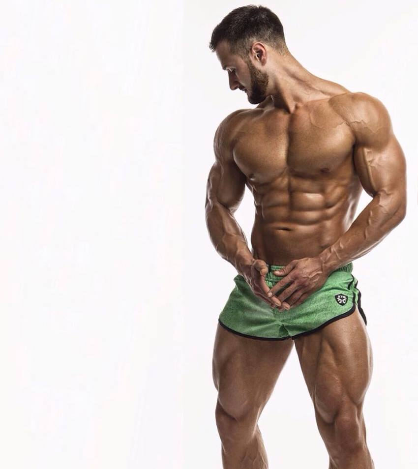 Emil Goliath posing for a photoshoot in green shorts, looking ripped and muscular