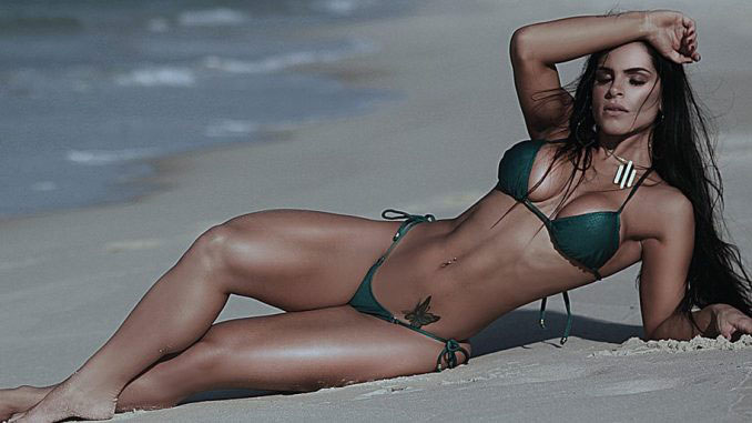 Fran Petersen posing lying down on a beach.