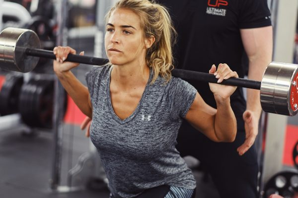Gemma Atkinson doing squats with her personal trainer behind her