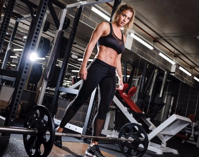 Gemma Atkinson standing by the bar in the gym and looking at the camera