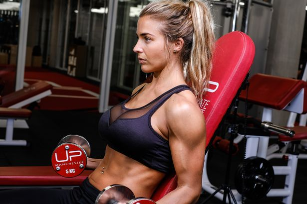 Gemma Atkinson training her arms with dumbbells on an incline bench