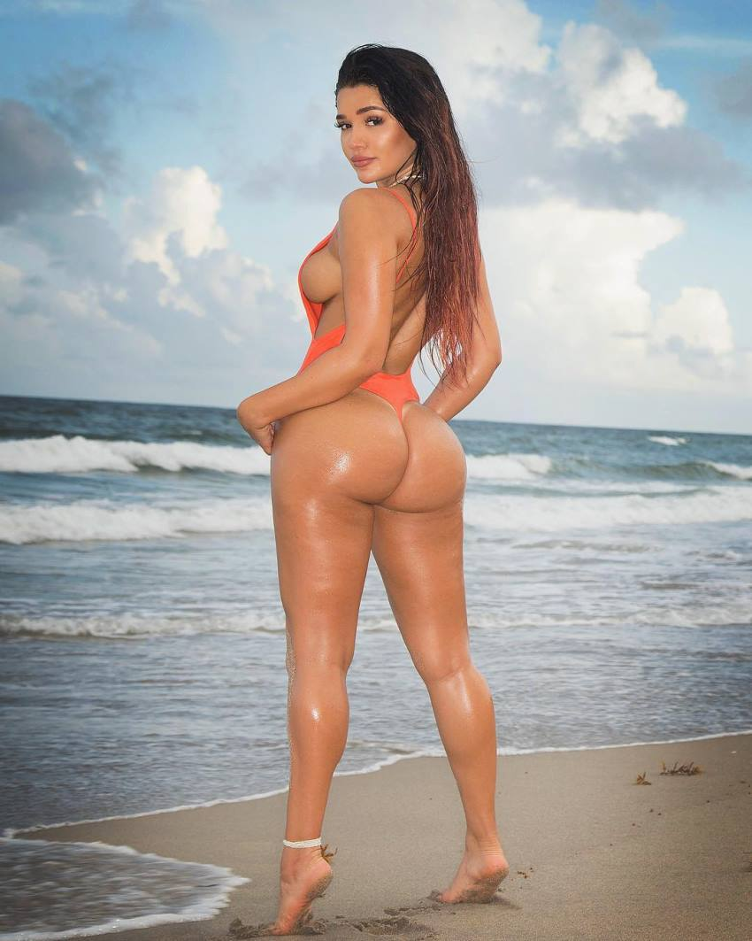 Genesis Lopez standing on her toes by the beach, displaying her incredible legs and glutes