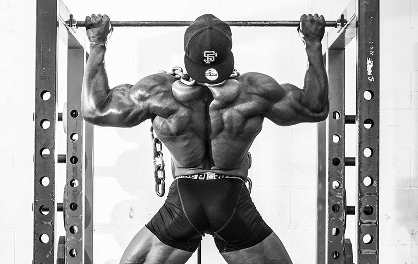 Gerald Williams performing weighted pull ups with a chain on his shoulders.