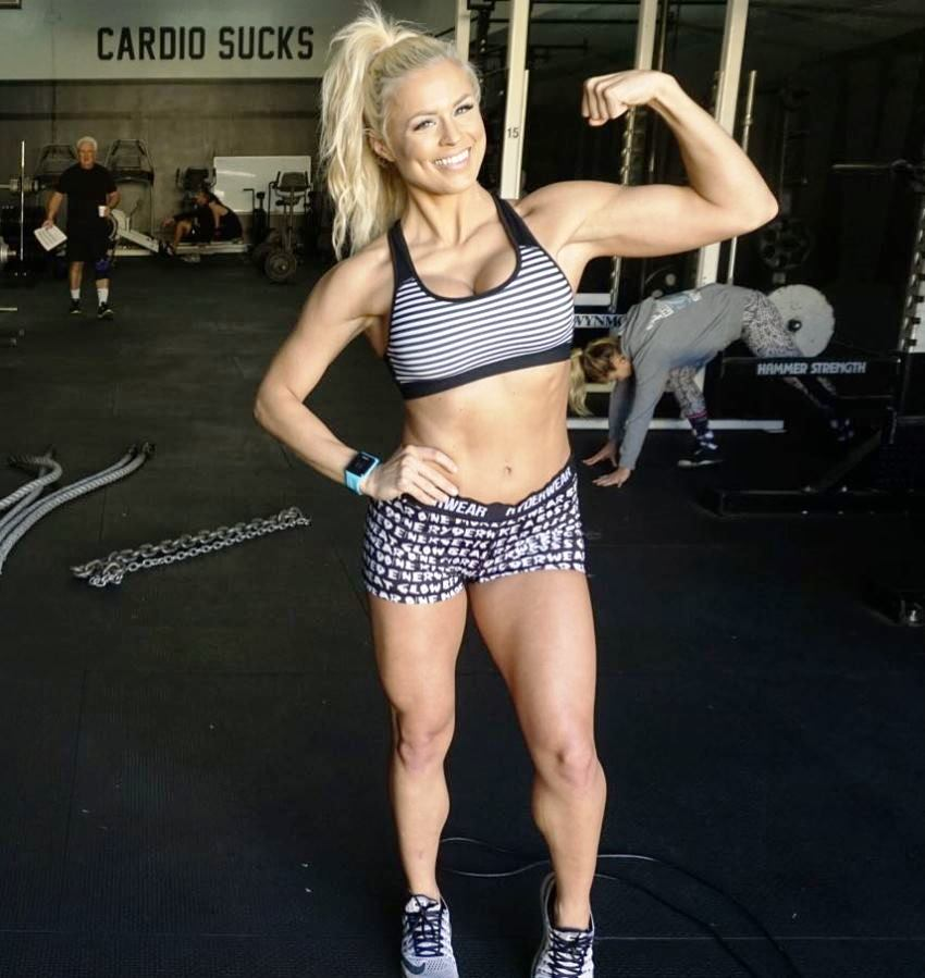 Jen Heward flexing her biceps for the camera, looking fit and ripped