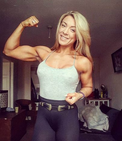 Jess Clutterbuck flexing her biceps and smiling