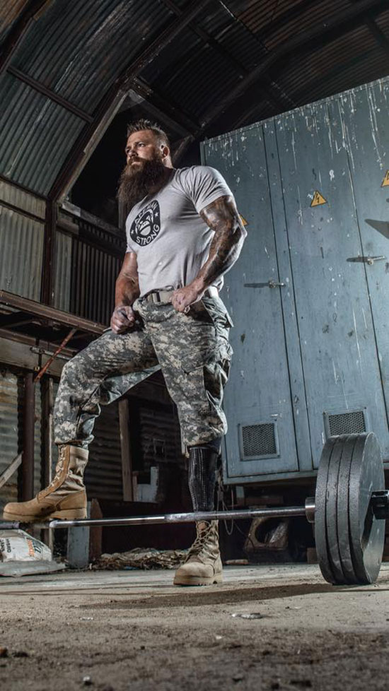 KC Mitchell stood with his foot on a barbell with is army gear on.