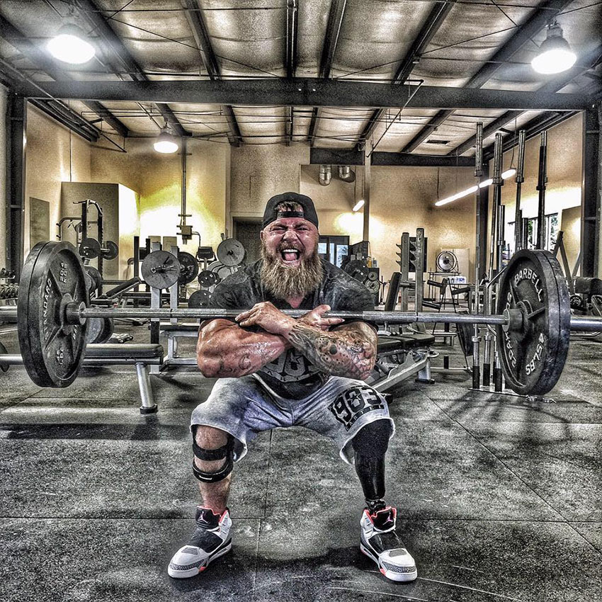 KC Mitchell in the gym holding a barbell with crossed arms.