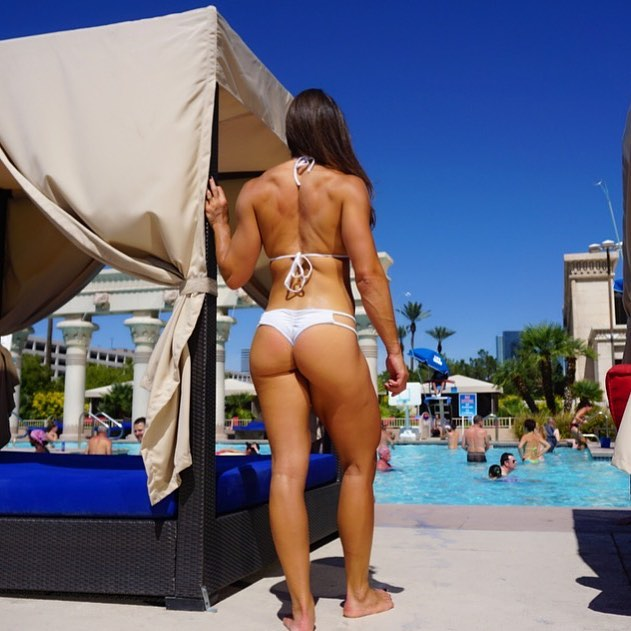 Kristen Graham standing near an outdoor pool, her glutes, back, and legs looking awesome