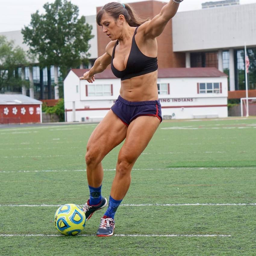 Kristen Graham kicking a football ball, looking ripped and muscular