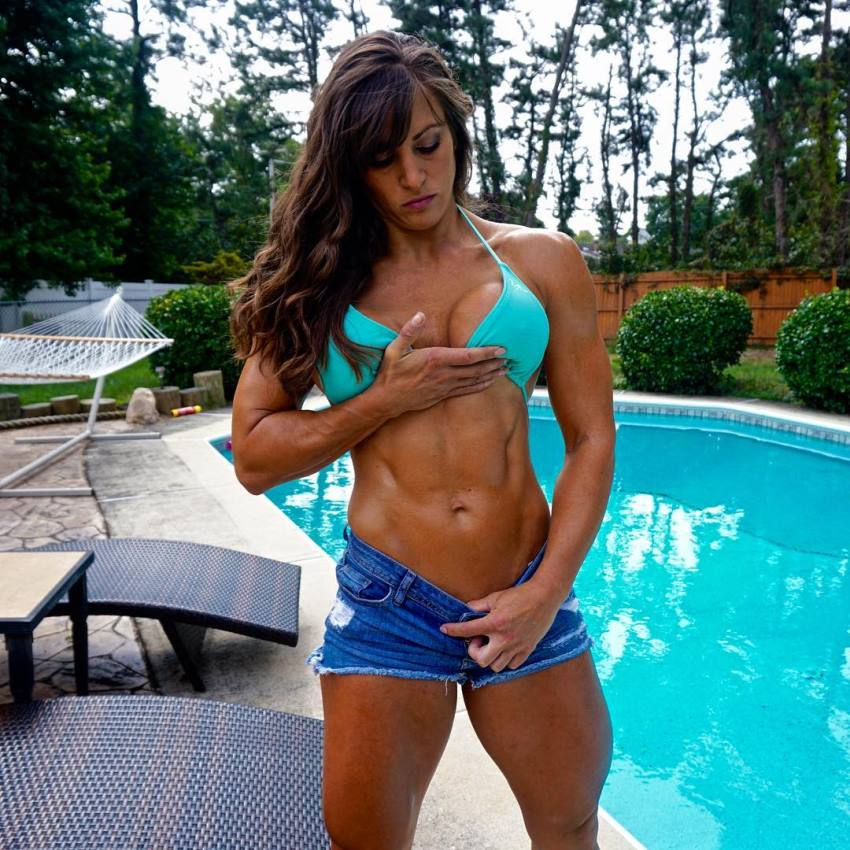 Kristen Graham flexing her abs by the pool for the camera