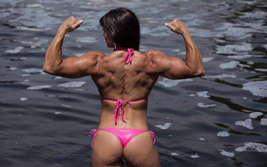 Kristen Graham doing a back double biceps pose whilst standing half-way into the sea