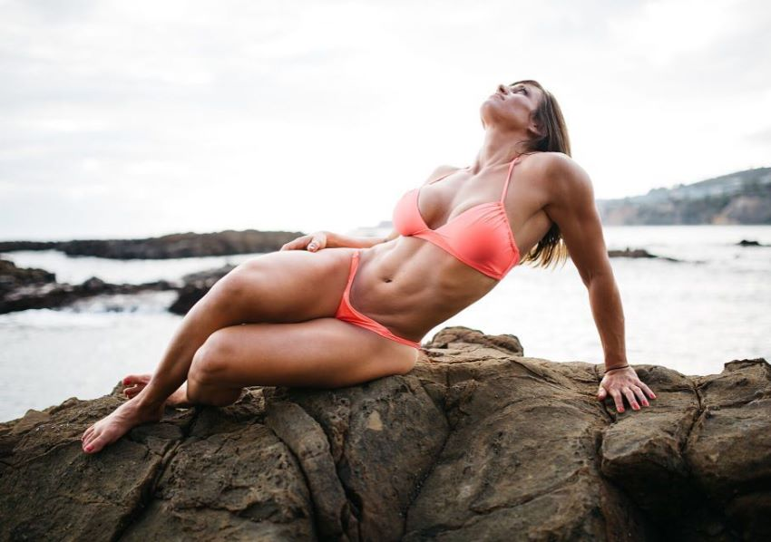 Kristen Graham lying on the rock by the beach in a red bikini, looking fit