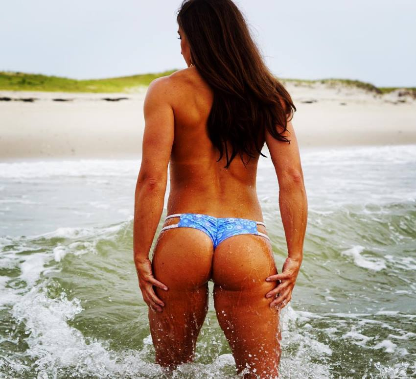 Kristen Graham standing half way in the sea, showing her muscular back, glutes, and legs