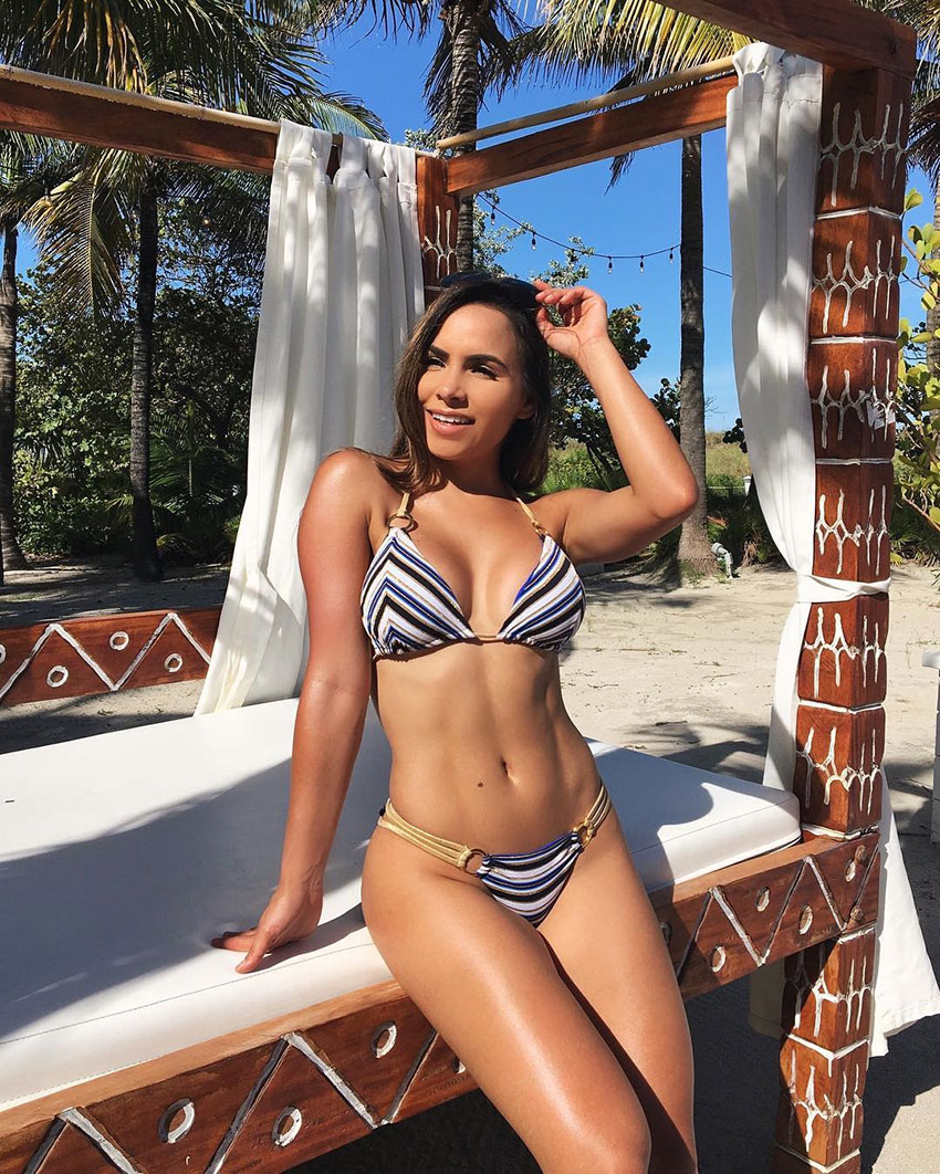 Lisa Morales on a beach stood by a sun bed.