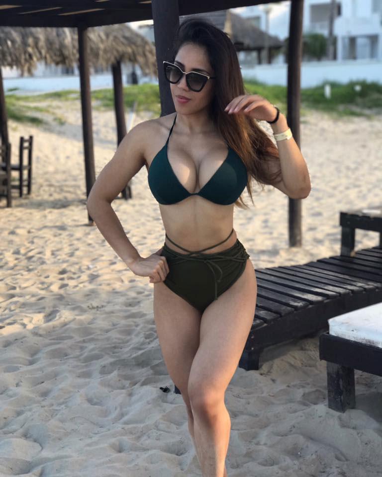 Liz Calles posing on the beach in a bikini.