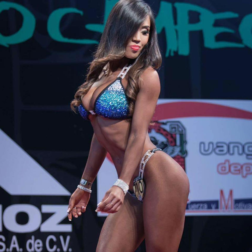 Liz Calles on stage posing at a bikini competition.