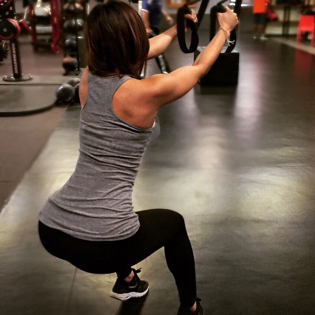 Liz Calles exercising in the gym with a suspension trainer.