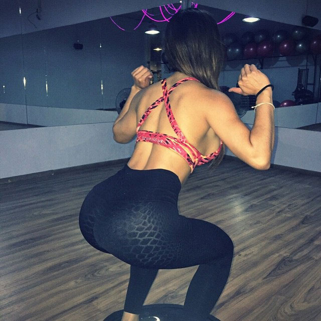 Liz Calles performing a squat in the gym.
