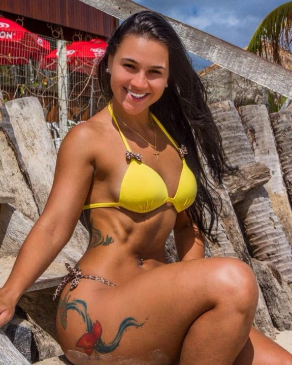 Lorrane Ottoni smiling at the camera, being in yellow bikini, looking fit