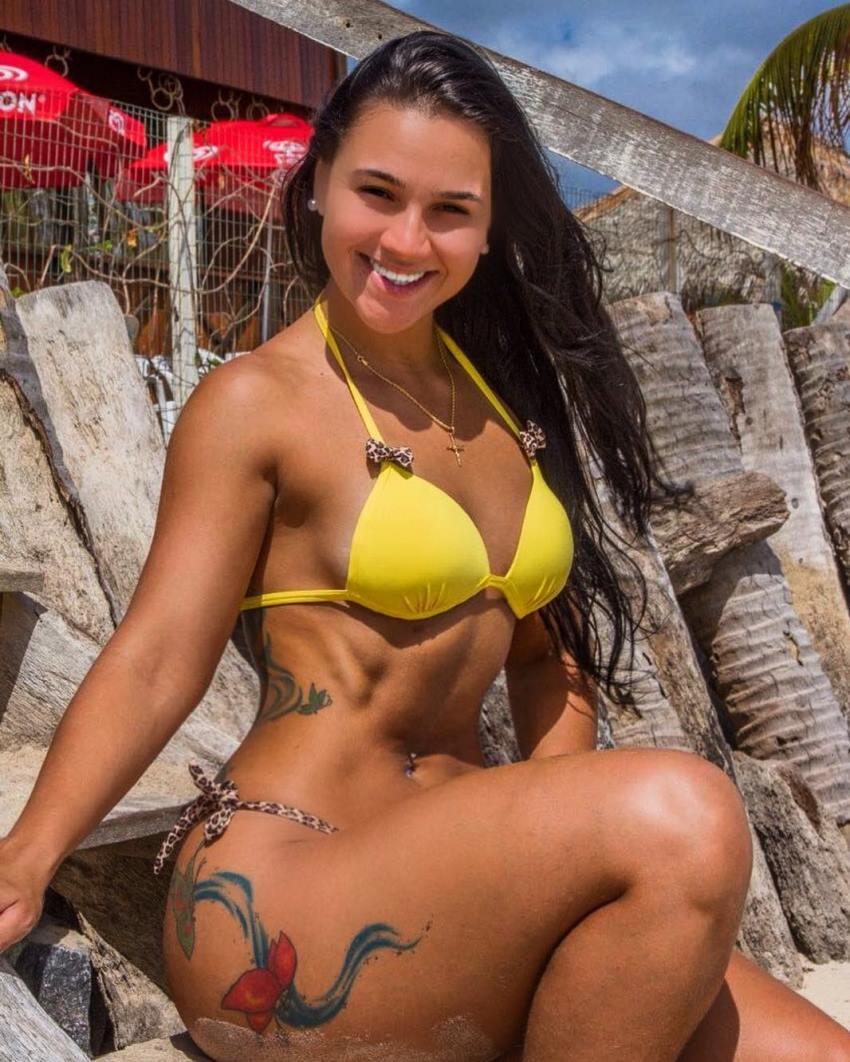 Lorrane Ottoni smiling at the camera, being in yellow bikini, looking fit